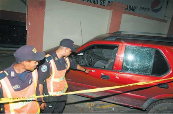 Un par de policías observan el vehículo en el que encontraron a uno de los más de cien abogados que han sido asesinados en el último lustro en Honduras. La Prensa Cortesía El Heraldo de Honduras