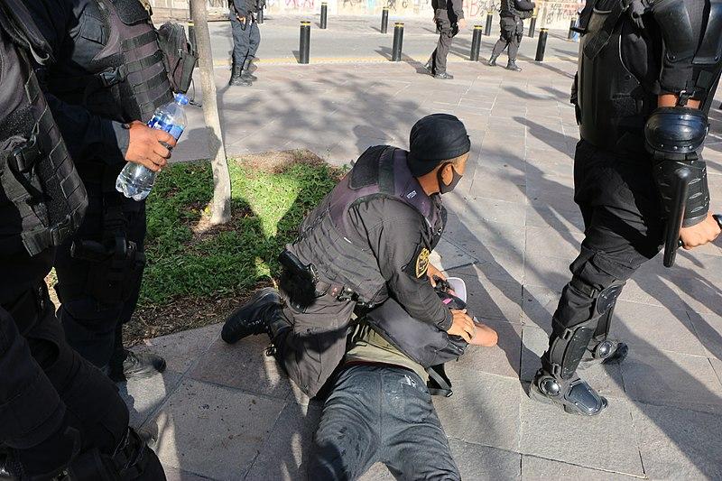 Un policier maintient un homme à plat ventre en utilisant son genou sur sa nuque